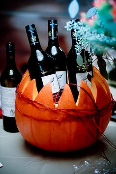 A festive pumpkin chills the wine on a fall party table.
