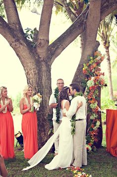 Tangerine bridesmaid dresses and decor add to the tropical feel of this destination wedding.
