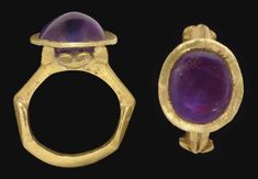 A ROMAN GOLD AND AMETHYST FINGER FING   CIRCA 3RD CENTURY A.D.   The solid cast hoop flat on the interior, carinated on the exterior, the sides voluted, merging with grooved shoulders, expanding toward the bezel, with four prongs supporting the oval bezel, with peltae on either side, set with a cabochon amethyst
