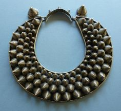 A Miao neckring consisting of a silver plate to which are attached four rows of small cones, the ends of which are intended to ward off evil spirits. Thus this piece has not only great aesthetic power but also profound belief and emotion underlying its creation - a characteristic of ethnic (and tribal) art in general, and something to which a growing body of people today are strongly attracted in a modern world considered too superficial and materialistic.