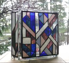 A brilliant stained glass light to enjoy in two different patterns. Done on both sides of a glass block in shades of blues, purples plum, white, greens, a pale pink and a clear textured glass in a geometric pattern on one side and an art deco type design on the other. Photos were taken