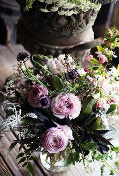 purple, pink and gray flower arrangement of ranunculus, lilac, sweet peas, geranium, jasmine, anemones, dusty miller and crabapple