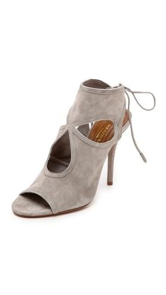 Sexy Thing Cutout Sandals. A cloverleaf cutout gives these soft suede Aquazzura booties a touch of modern, feminine chic. Polished aglets accent the lace-up closure behind the heel. Covered stiletto heel and leather sole.