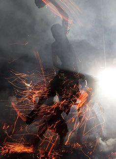 A Balinese man hits fire during a ritual ahead of Nyepi day in Ubud Gianyar, Bali.