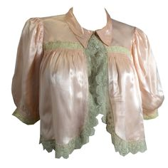 "1930s peach silk satin bed jacket with ecru lace trim, puffed sleeves, loop and button closure. No labels, no flaws. Measures 14"" shoulders, 38"" bust, open waist, 17"" long, 13"" sleeves"