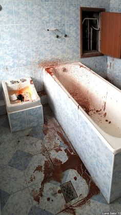 A bathroom of an abandoned mental asylum which seems to have years of dried blood oon the floor.