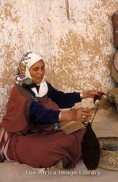 Berber woman spinning wool in Berber troglodyte (underground) homestead, Matmata, Tunisia