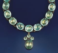 "An 18th century paste necklace   Composed of a line of oval mixed-cut ""aquamarine"" coloured pastes suspending a central pear shaped and circular paste four stone drop, to a velvet fastener, in gilt metal mounts with coloured foil backs"