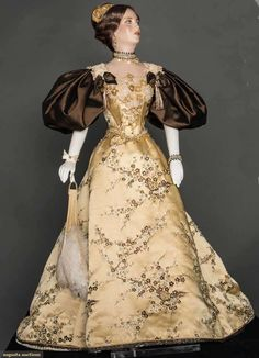 """29"""" figure, period accurate 1893 ball gown created & hand sewn by fashion designer John Burbidge: gold silk satin brocaded w/ plum blossoms & hand applied pearls & beads, pearl & bead jewelry & hair piece, includes hand fan, undergarments & shoes, all excellent. This is one of 75 """"ladies"""" each costumed in a 1860 through 1914 unique ensemble, as seen in the book """"Les Petites Dames de Mode"""" & numerous museum presentations throughout the U.S."""