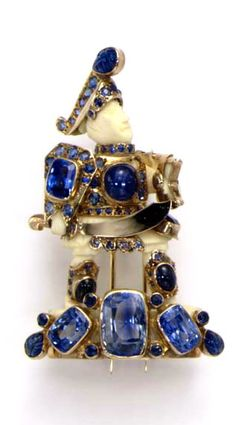 AN IVORY AND SAPPHIRE WARRIOR BROOCH  Designed as a carved ivory body adorned in vari-cut sapphires and gold armour, with a gold sword, standing on a carved, cabochon and cushion-cut sapphire platform, mounted in gold