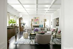 """""""Float furniture away from the walls: It creates more intimate seating,"""" designer Betsy Burnham says. She did just that in the living room of this California house. The console table separating back-to-back sofas is decked with vintage goddess figurine lamps and Chinese monkeys """"for a Tony Duquette, William Haines flavor."""" Sellarsbrook rug, the Rug Company. Rectangular Cocktail Table, Baker.   - HouseBeautiful.com"""