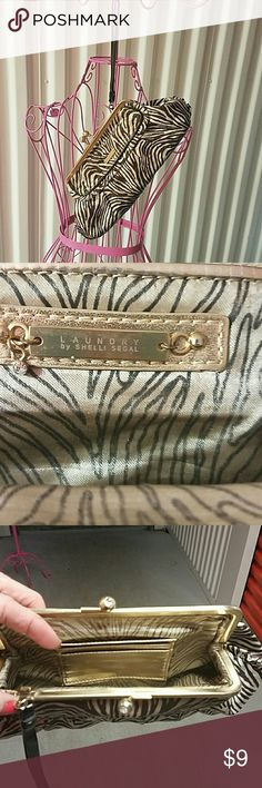 "Vintage ""LAUNDRY CLUTCH by SHELLI SEGAL VINTAGE, ""Laundry brown and cream colored ZEBRA PRINT"" CLUTCH, by SHELLI SEGAL "",has 2 beautiful crystal beads to snap open and close the clutch. Does have some wear on the makers mark gold tag on front, but other than that great shape for the age.  Trying to clear out my closet, MAKE OFFER!! Approximately 10 inch long by 5 inches tall Shelli Segal Bags Clutches & Wristlets"