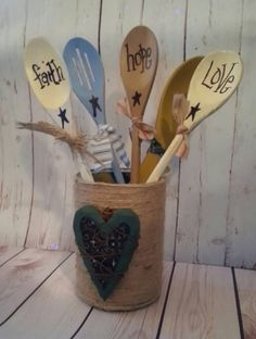 Wood spoon bouquet    Upcycled tin can wrapped with natural juted with heart ornament on front. A collection of wood spoons painted with acrylic paint finished off mix of homespun ticking and burlap fabric. Words Faith Hope Love and prim stars    A great primitive display for your kitchen    Spoons are not for food use    Thanks for stopping by