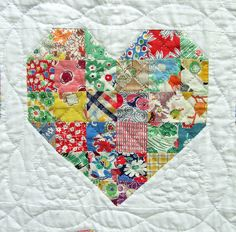 could do small pieces of baby clothes to make a more contemporary quilt.  offset the heart on a solid.