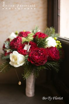 Wedding Flowers - Bridal Bouquet of red and white garden roses accented with winter foliages and berries. We included 2 small lockets with sentimental family pictures for the bride.