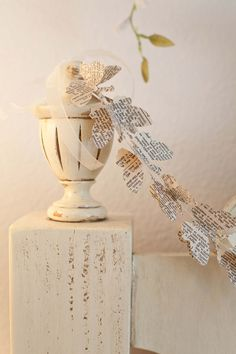 Add a touch of spring with this whimsical butterfly garland. Butterflies are cut from a vintage dictionary and stacked two together to create a three dimensional effect. Drape on your mantel, headboard or window, or group many strands together to create a virtual butterfly curtain.