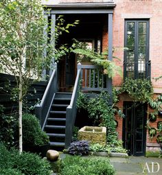 Julianne Moore - The painted trim of the 1905 house is complemented by matte-black accents found throughout the garden; the window box is planted with English ivy, and a purple sweet potato vine adds a splash of color at the foot of the stairs.
