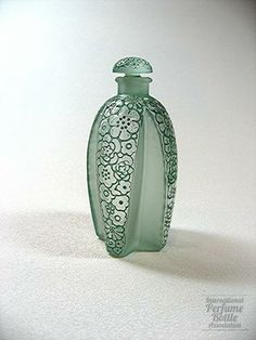 "Toutes Les Fleurs, Gabilla, Rene Lalique, France c. 1926. Clear and frosted cruciform bottle with green patina flowers molded on the raised panels and stopper. This bottle was also produced in other colored patinas. Title translates ""All the Flowers."""