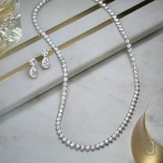 Diamond Necklace Timeless, elegant, and endlessly versatile, the House's Straightline Necklace and Diamond Drop Earrings perfectly complement any occasion. Diamond Drop Earrings, Diamond Pendant Necklace, Diamond Jewelry, Diamond Necklaces, Gold Jewellery, Locket Necklace, Necklace Set, Arrow Necklace, Gold Necklace