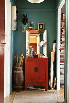 """Walls that look emerald or teal—depending on the light—create a jewel-box effect that makes this small space feel like a tucked-away treasure. """"While there may be many things in this nook, a sense of organization is accomplished by grouping them together by object or function,"""" Holly Becker, author of Decorate Workshop, says."""
