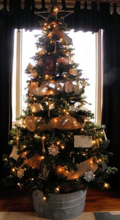 Country Christmas tree. Instead of a tree skirt, why not a bucket? I actually really like this. Although, I would have a larger tree and change it up a bit. I love rustic country decor. Very cute!: