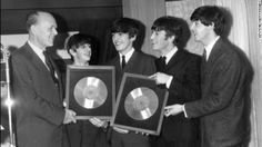 """Sir Joseph Lockwood, chairman of EMI Music, presents The Beatles with two silver records for their albums """"Please, Please Me"""" and """"With The ..."""