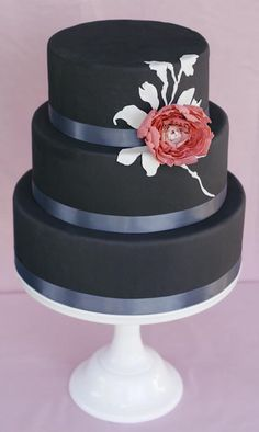 Modern black and white wedding cake with pink flower