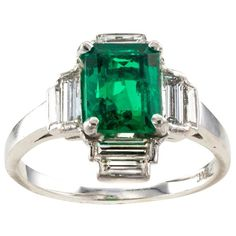 """Art Deco Emerald Diamond Platinum Cluster Ring... resplendent emerald-cut Emerald weighing approximately 1.50 carats, framed within a unique arrangement of eight baguette diamonds totaling approximately 0.90 carat, approximately G color, VS clarity. An easy to fall in love with cool-green and very bright emerald, mounted in platinum, ring size approximately 5 1/4, approximately 1/2"""" long vertical to the fingernail. Vintage Art Deco emerald and diamond ring circa 1930."""