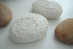 Website couldn't be found, but I think the rock is encased in air dry clay and impressed with lace.
