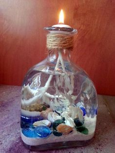 liquor bottle repurpose coastal candle, crafts, how to, repurposing upcycling by janie Empty Liquor Bottles, Liquor Bottle Crafts, Bottles And Jars, Patron Bottle Crafts, Patron Bottles, Reuse Plastic Bottles, Wine Bottle Candles, Beach Memory Jars, Anchor Crafts