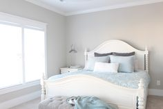 Sherwin Williams Repose Gray in a subtle beach or coastal theme bedroom with white furniture