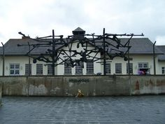 An art memorial depicting intertwined bones and bodies adorns the exterior of the Dachau Concentration Camp museum.  (photo by Sara Tallerico)