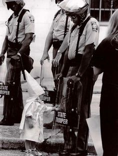 The Trooper is black. Standing in front of him and touching his shield is a curious little boy dressed in a KKK hood and robe. In this picture innocence is mixed with hate, the irony of a black man protecting the right of white people to assemble in protest against him.