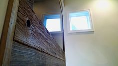 The TV has been built into a reclaimed barn wood wall. The small awning windows give the room a hint of modern design.