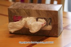 Use a recycled tissue box to store plastic grocery store bags.