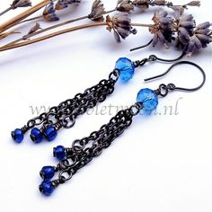 Long earrings with blue fire polish glass rondels, black aluminum chains and seed beads at the ends.