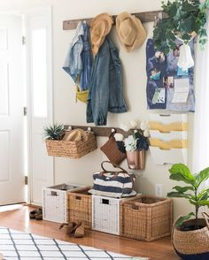 House Tour: A Room For Every Taste from Wayfair! From glam to mid-century to global and back again, this home proves you don't have to stick to one style to create a polished look. Here, a coat rack paired with various wicker storage boxes and baskets create an organized entryway.