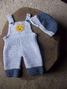 Conjunto de macacão e boné confeccionados em crochê. <br>detalhes - solzinho em crochê. <br>cor - azul <br>tamanhos - 1 a 3 / 3 a 6 / 6 a 9 meses