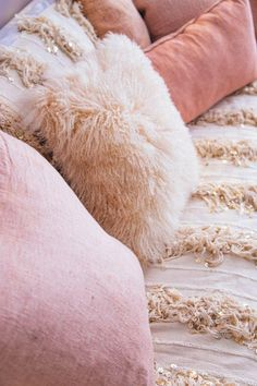 Pretty pink pillows in velvet and Mongolian sheep fur look ultra-feminine and cozy on this  dyed blush pink Moroccan wedding blanket that has a bit of sparkle! Love this style idea for styling a super girlie and sophisticated sofa -- would also look amazing on a daybed or bed!