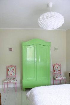A bright, minty-colored armoire flanked by a pair of floral chairs introduces a modern garden vibe to an otherwise starkly white room.   Source