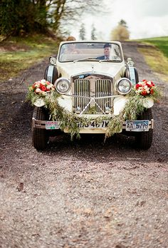 Brides.com: . This 1930s-inspired wedding obviously required an amazing vintage getaway car. This couple topped theirs with a greenery garland and two bundles of orange-and-red flowers that were nearly identical to the bride's lush bouquet.