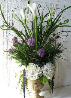 White hydrangeas, while calla lilies, purple thistle and allium, hanging vines and curly grasses