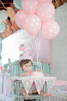 Pink polka dot balloons, vintage high chair painted with chalk paint, and pennants on high chair tray.