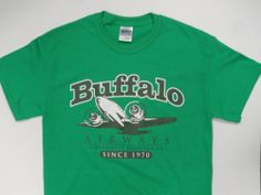 """This high quality green coloured cotton with the art deco DC-3 image in black and white is our best selling tee shirt. This stylized tee will have you looking your best in the traditional Buffalo green.  The Classic DC-3 tee continues to outsell all of our other tees. We suggest that you join the crowd and GO GREEN WITH BUFFALO!Size Measurements:    Small  Medium  Large  X-Large  2XL                         Length 28""""      29""""       30""""      31""""        ..."""