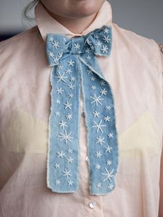 Make a ribbon bow from denim scraps. Cut a strip. fray edges and embroider... such a great idea