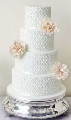 For a minimalist touch, stick to one simple pattern for the piping and adorn each tier with a single flower, as shown on this cake. Photo via The Abigail Bloom Cake Company .