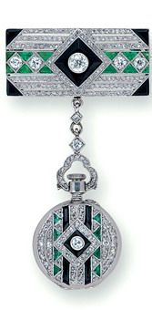 An Art Deco Diamond, Onyx and Emerald Pendant Watch, circa 1920 suspended by a plaque brooch of geometric design, centering a diamond collet upon a French-cut onyx and diamond lozenge surround, between calibre-cut emerald and carre-set diamond shoulders, to rows of small rose-cut diamonds and calibre-cut onyx corners, from a diamond line and trefoil bail, to the similarly decorated pendant, the verso with an openface watch with circular white dial.
