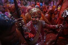 Hindu men from the village of Nandgaon, smeared with colors, play holi at the Ladali or Radha temple before taking out a procession for the Lathmar Holi festival, at the legendary hometown of Radha, consort of Hindu God Krishna in Barsana, India.
