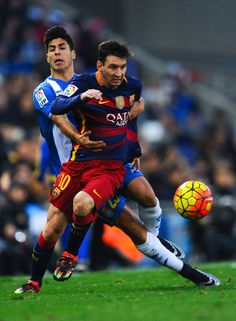 Lionel Messi of FC Barcelona competes for the ball with Marcos Asensio of RCD Espanyol during the La Liga match between RCD Espanyol and FC Barcelona at Cornella-El Prat Stadium on January 2, 2016 in Barcelona, Catalonia.