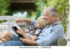 Grandfather reading book with grandson - stock photo